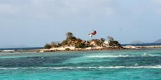 Skipper surfing over an island inhabited by a solitary rasta